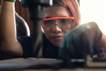 Diverse female certified industrial engineer operating factory drill machinery - Engineering student concentrating on production drilling for manufacturing business - Training and learning concept